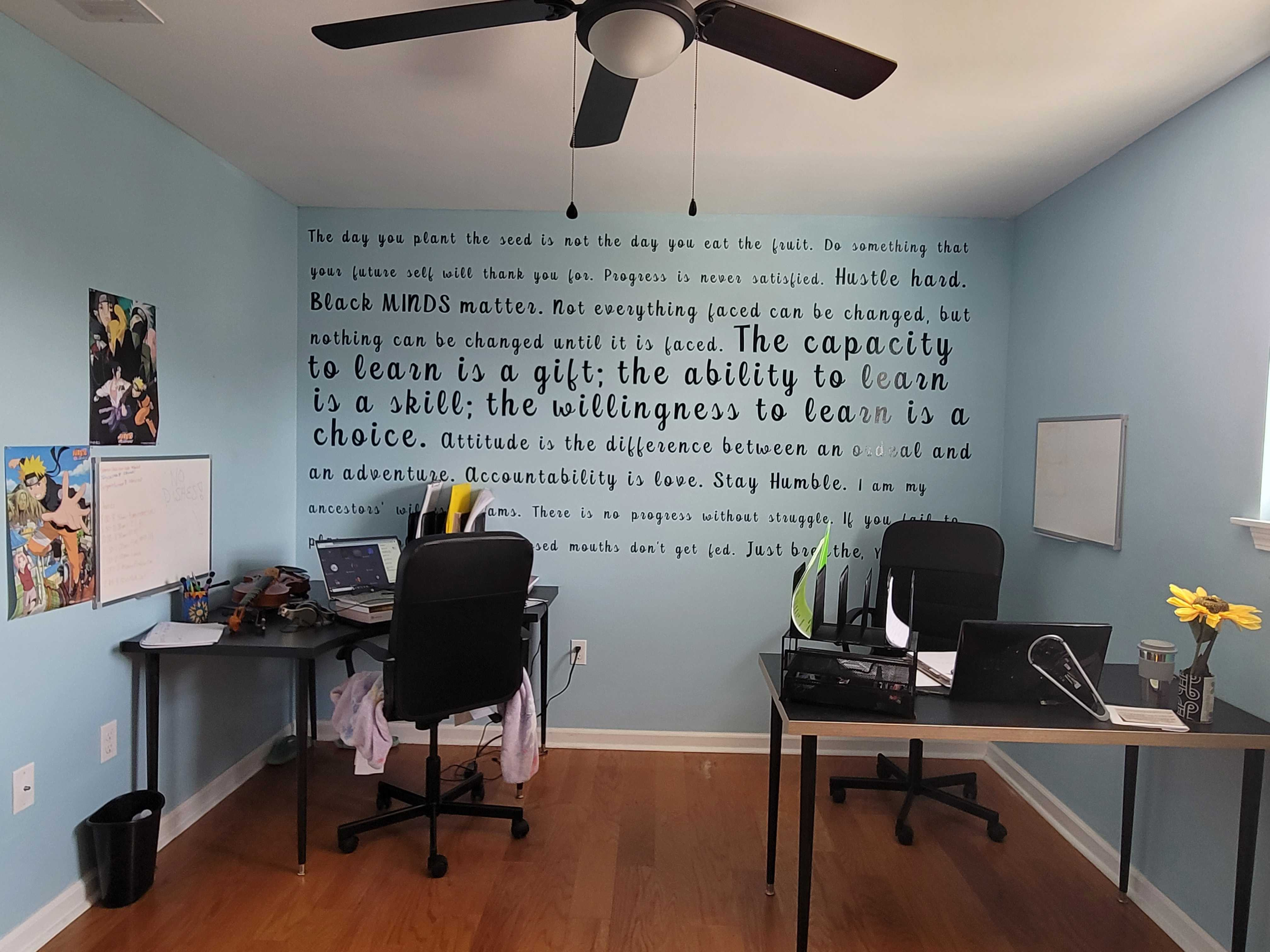 A room with desks and a wall of inspiring quotes.