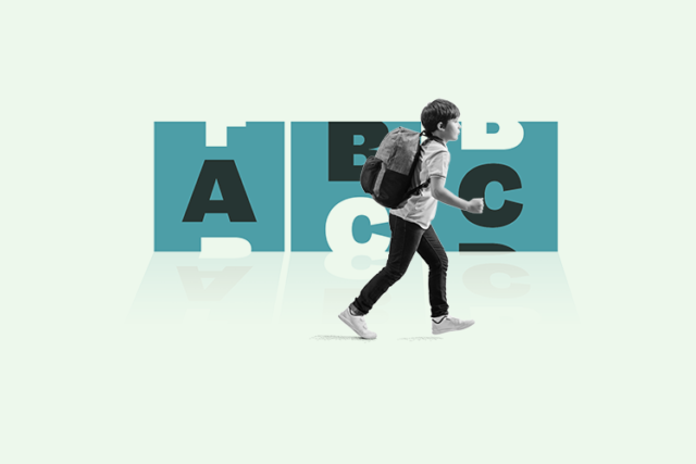 Boy with backpack running in front of ABC banner